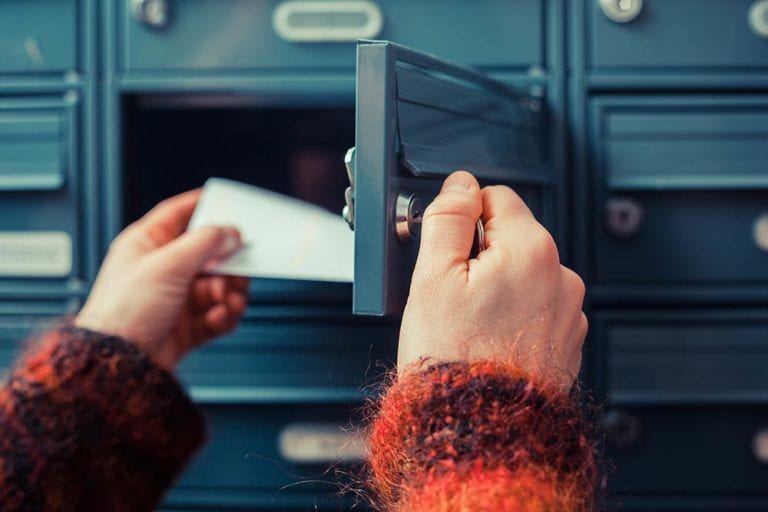 Person checking post office box for mail